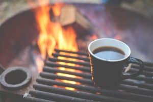 coffee cup heating up by camp fire